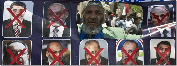 An Egyptian man holds a sign with portraits of Islamist leaders