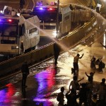 Riot police use water to disperse opposition demonstrators as they block the city's main highway in Caracas