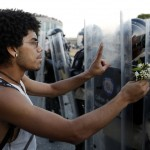 An opposition demonstrator gives flowers to a police as they block the city's main highway in Caracas