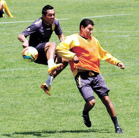 Atigrados. Luis Melgar (izq.) disputa un balón con Marcos Paz en una práctica.