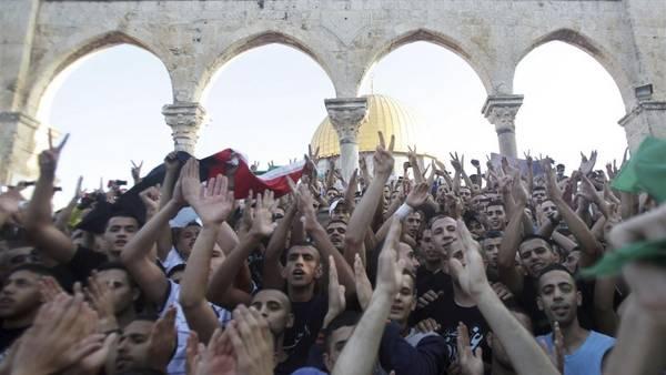 Un gurpo de palestinos realiza una protesta en apoyo a Hamas ldurante los rezos de la mañana que marcan el fin del Ramadán, en Jerusalén. (EFE)