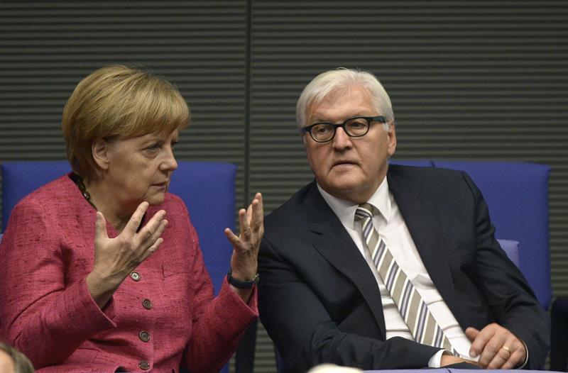 Canciller alemana, Angela Merkel (i), conversa con el ministro alemán de Exteriores, Frank-Walter Steinmeier (d), durante una sesión extraordinaria del parlamento alemán en Berlín. EFE