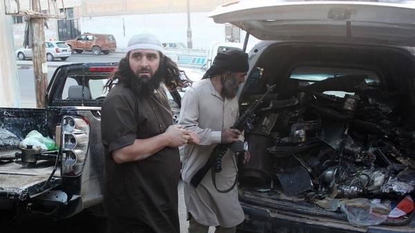 Combatientes del Isis cargan en un vehículo lo que dicen son los restos de un drone norteamericano estrellado en Raqqa. (AFP)