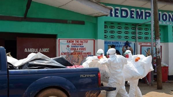 Miembros de la Cruz Roja de Liberia cargan el cuerpo de una víctima de ébola en un barrio de Monrovia, Liberia. (AFP)