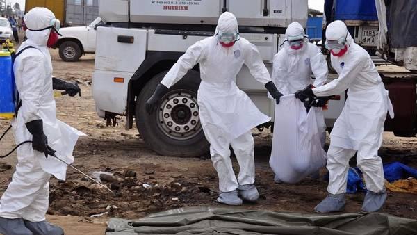 Trabajadores sanitarios cargan el cuerpo de un hombre que murió de ébola en las calles de Monrovia, Liberia. (AP)