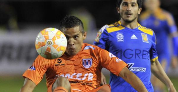 Jorge Cuéllar intenta proteger el balón mientras es encimado por el argentino Álvarez del equipo de Tigres