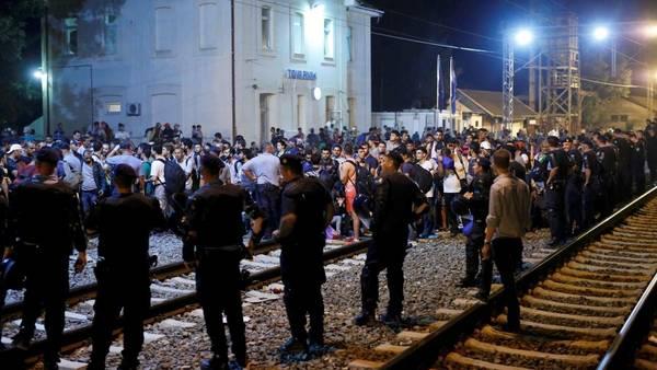 Custodia. La policía croata controla a un grupo de inmigrantes en Tovarnik. /Reuters