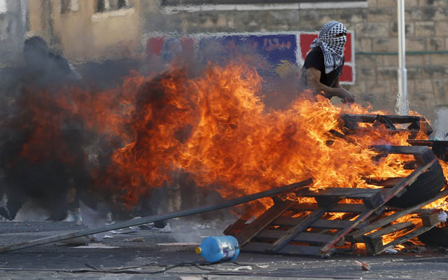 Palestinian stone throwers stand next to a burning wood barrier during clashes with Israeli security forces in the Palestinian neighborhood of Shuafat in east Jerusalem on October 5, 2015 as violence spiked in east Jerusalem and the occupied West Bank. A new wave of violence has hit Israel and the Palestinian territories, prompting warnings of the risk of a third intifada similar to uprisings that began in 1987 and 2000. AFP PHOTO / AHMAD GHARABLI