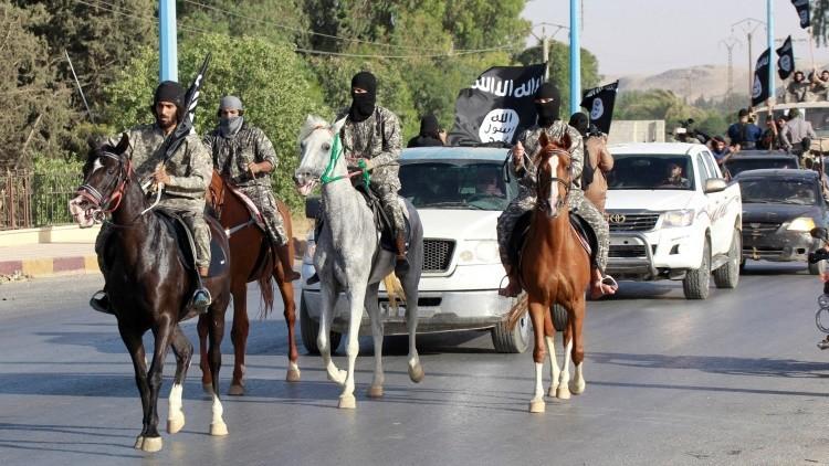 Militantes islamistas marchan por la calles de Raqqa, Siria