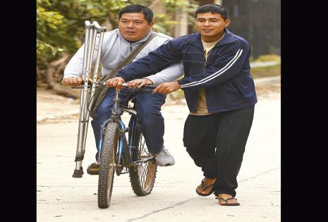En esta bicicleta le ayudan a salir a tomar micro. En su universidad sube todas las gradas sin problemas