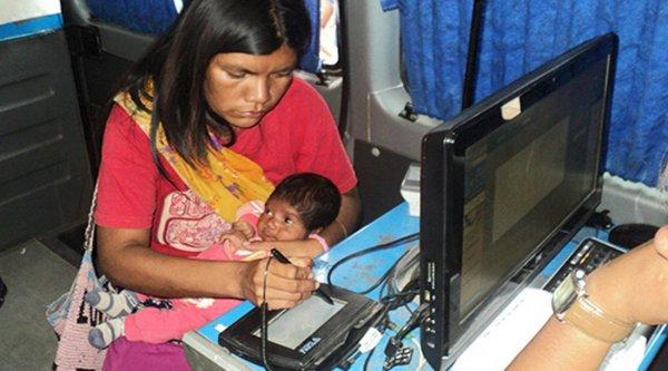 Una mujer, con su beba en brazos, tramitando documentos en Tartagal.