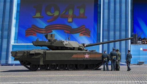 Oficiales del ejército ruso hablan sobre un tanque con un miembro de la tripulación del T-14 Armata en la plaza Roja de Moscú durante los preparativos para el ensayo general del desfile militar del Día de la Victoria que se celebrará en la plaza moscovita el 9 de mayo para celebrar los 70 años de la victoria del país en la IIGM, en Moscú, Rusia, el 7 de mayo de 2015. (Foto AP/Alexander Zemlianichenko)