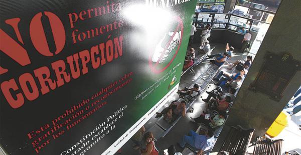Desde las puertas del Palacio de Justicia se observan    letreros contra      la corrupción
