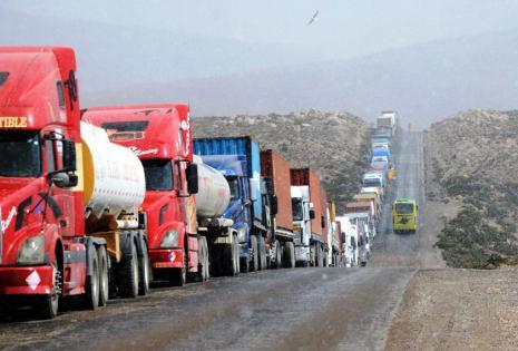 Camiones varados se ven en la frontera con Chile en Tambo Quemado,  funcionarios de aduanas chilenas van a la huelga, 26 de mayo de 2015. Decenas de conductores y sus familiares protestaron en frente del consulado del Chile en La Paz el jueves, exigiendo