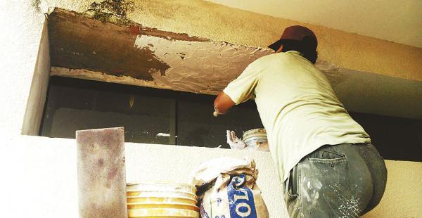 Un trabajador, contratado por la Alcaldía, pinta un colegio del D13