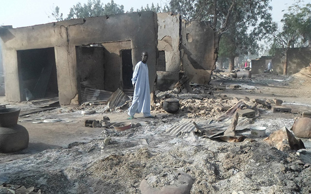 A man walks past burnt out houses following an attack by Boko Haram in Dalori village 5 kilometers (3 miles) from Maiduguri, Nigeria, Sunday Jan. 31, 2016. A survivor hidden in a tree says he watched Boko Haram extremists firebomb huts and listened to the screams of children among people burned to death in the latest attack by Nigeria¿ s homegrown Islamic extremists. (AP Photo/Jossy Ola) Nigeria Boko Haram
