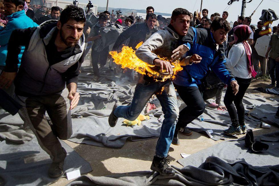 Un refugiado corre este martes tras prenderse fuego durante una protesta en un campamento en la frontera greco-macedonia.