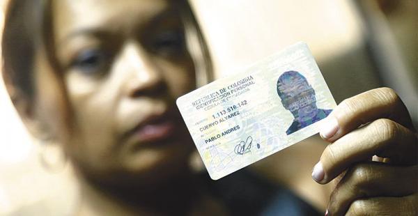 Vivian sosteniendo la fotografía del documento de identidad de su hijo