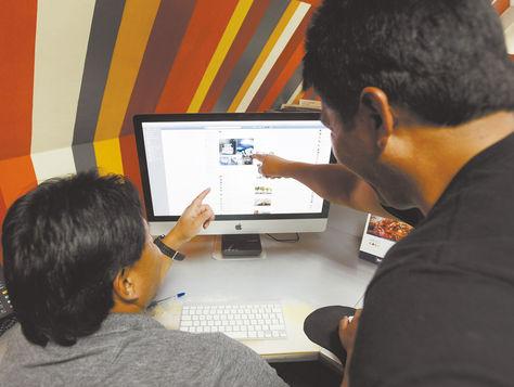 Producción. Dos personas observan las ofertas publicadas en la cuenta Autos Chutos Bolivia.