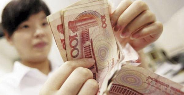 Una mujer muestra billetes de la moneda china. La devaluación abarata los productos chinas en el mundo