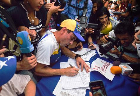 El líder de la oposición venezolana y gobernador del estado de Miranda, Henrique Capriles, firma el formulario para activar el referéndum sobre la reducción de mandato del presidente Nicolás Maduro corta, en Caracas.