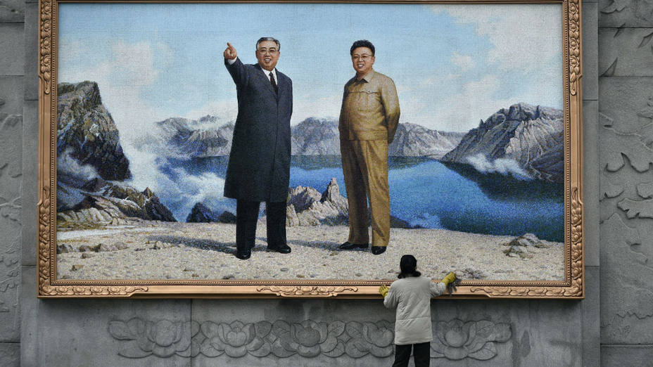 Una mujer limpia un gran mosaico que muestra los retratos de los antiguos líderes Kim Il-sung y Kim Jong-il en el Estudio de arte Mansudae en Pionyang (Corea del Norte) (Efe)