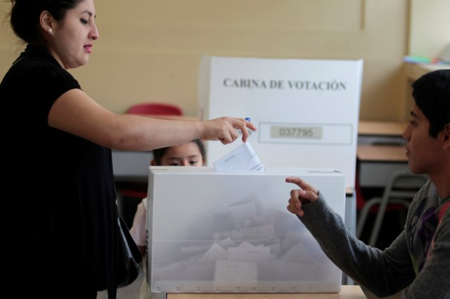 A woman deposits her vote in a ballot box in Peru