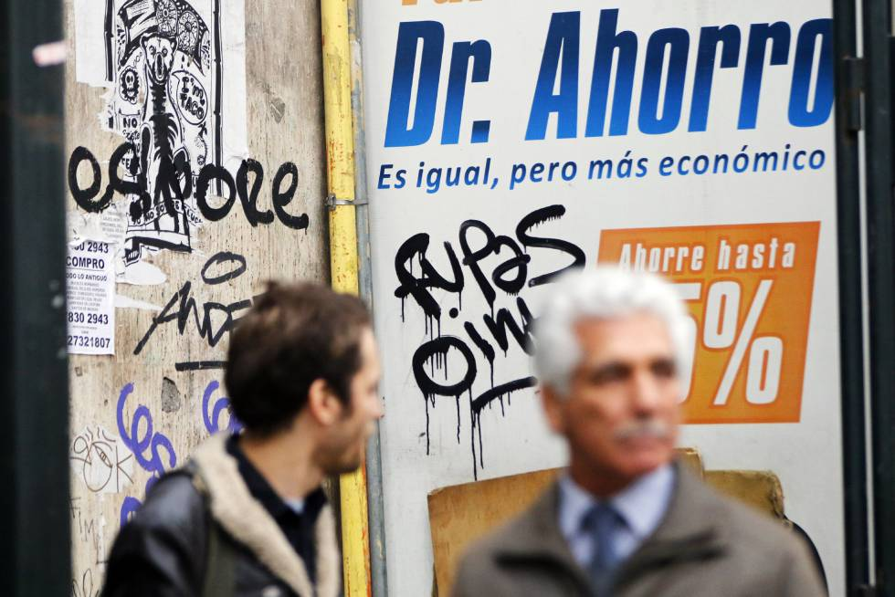 Dos personas caminan frente a un anuncio en Santiago de Chile el pasado martes.