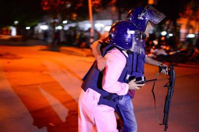 Ayuda. Un policía herido durante el operativo es llevado por un compañero hacia una ambulancia. /AFP - STR