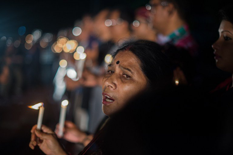 "A Bangladeshi woman sings a song for peace as she and dozens others gather in a park in for a candle-light vigil following an attack and seige in Dhaka on July 3, 2016. Bangladesh said July 3 the attackers who slaughtered 20 hostages at a restaurant were well-educated followers of a homegrown militant outfit who found extremism ""fashionable"", denying links to the Islamic State group. As the country held services to mourn the victims of the siege in Dhaka, details emerged of how the attackers spared the lives of Muslims while herding foreigners to their deaths. / AFP PHOTO / ROBERTO SCHMIDT"