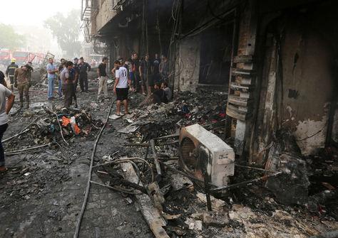 Iraquíes inspeccionan los daños en el lugar del atentado suicida con coche bomba reivindicado por el grupo Estado Islámico.