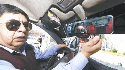 Pablo Yáñez, radiotaxista de Magistrado, muestra la cámara de seguridad instalada en su retrovisor.