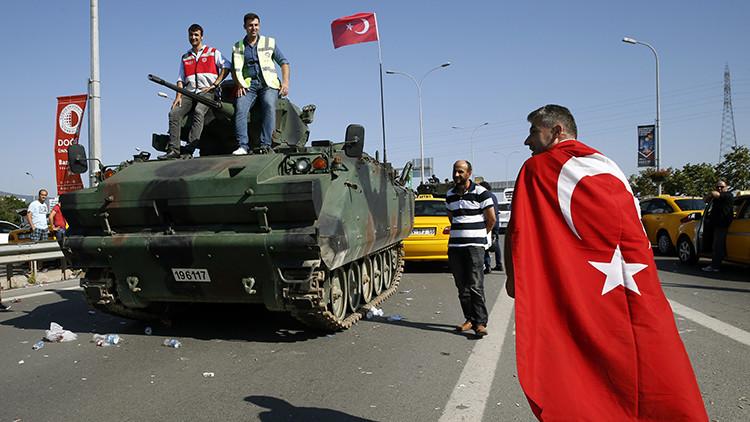 Un hombre pasa junto a un vehículo militar cerca del aeropuerto Sabiha Gokcen de Estambul, Turquía.