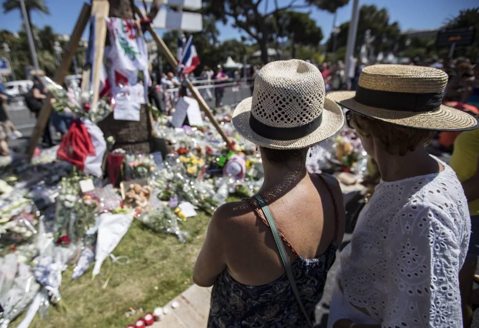 Varios turistas, ante los ramos de flores colocados en el lugar del atentado de Niza.