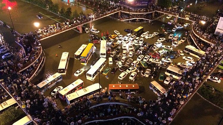 Vehículos varados en un cruce de caminos durante una fuerte lluvia en Xi