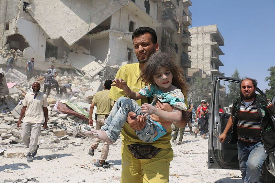 A Syrian man carries a child in the Maadi district of eastern Aleppo after regime aircrafts reportedly dropped explosive-packed barrel bombs on August 27, 2016. At least 15 civilians were reported killed when two bombs fell several minutes apart, near a tent where people were receiving condolences for those killed this week. / AFP / AMEER ALHALBI (Photo credit should read AMEER ALHALBI/AFP/Getty Images)