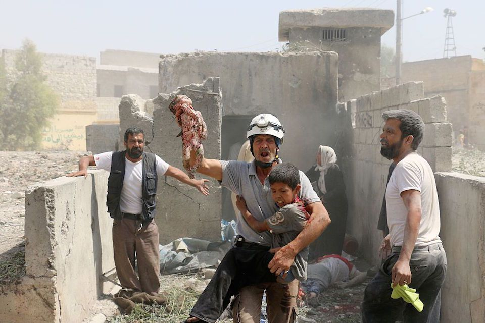 EDITORS NOTE: Graphic content / A Syrian rescue worker evacuates a dead baby and a wounded child as civilians search for victims in the Maadi district of eastern Aleppo after regime aircrafts reportedly dropped explosive-packed barrel bombs on August 27, 2016.At least 15 civilians were reported killed when two bombs fell several minutes apart, near a tent where people were receiving condolences for those killed this week./ AFP / AMEER ALHALBI        (Photo credit should read AMEER ALHALBI/AFP/Getty Images)