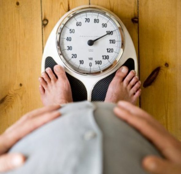 Man holding belly, with feet on weighing scales