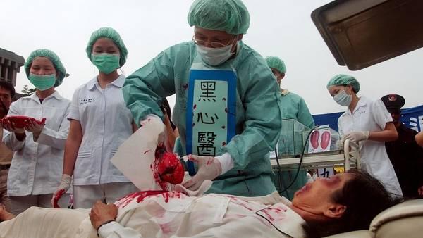 Los practicantes de Falun Dafa simulan la sustracción de órganos en un campo de trabajo chino para protestar por sospecha de abuso y asesinato de China. (AP)