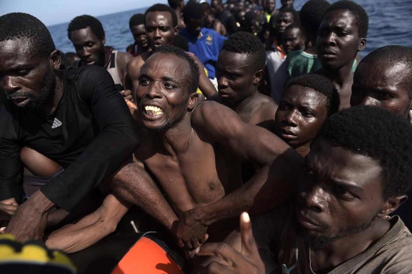 Los inmigrantes se arraciman en espera de ser traspasados a los barcos de auxilio
