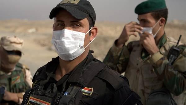 Barbijos. Soldados iraquíes se protegen del humo tóximo que emana cerca de la ciudad de Awsaja, en Irak, este sábado. I/AP