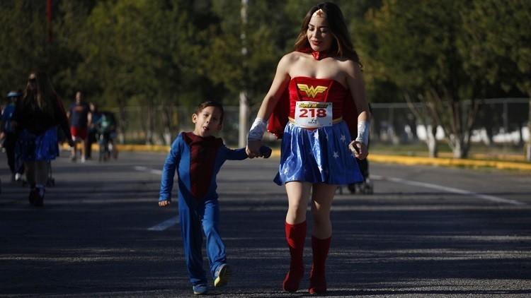 Una mujer disfrazada de Mujer Maravilla camina con su hijo con traje de Hombre Araña durante la carrera 'Superhéroes Corriendo Por Pequeños Inocentes' en el Chamizal Park en la Ciudad Juárez, México el 26 de octubre de 2014.