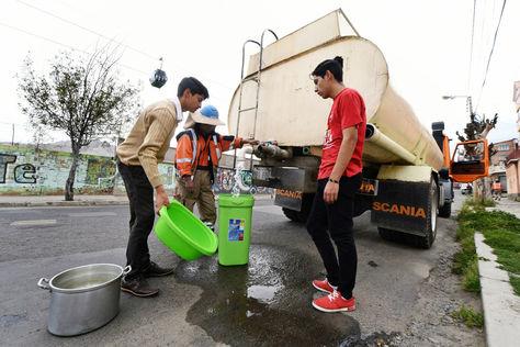 Vecinos de Alto Obrajes reciben agua de un camión cisterna.