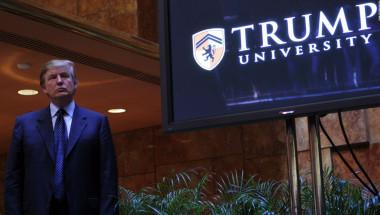 Trump al lado de un aviso de su controvertida universidad.