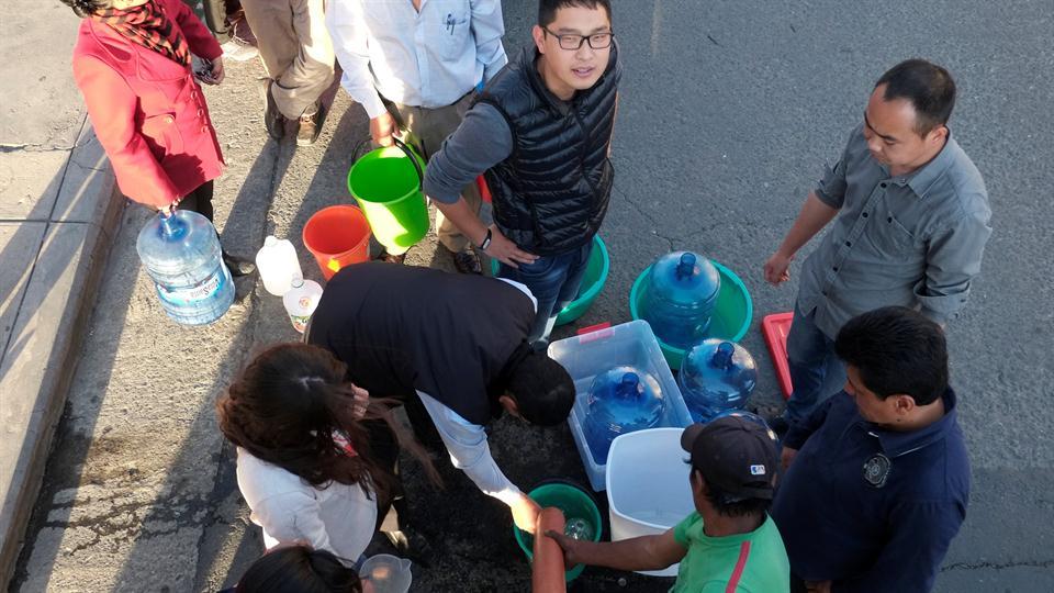 Es común ver grupos de personas con varios tachos para conseguir agua para cocinar o higienizarse. Foto: Reuters / David Mercado