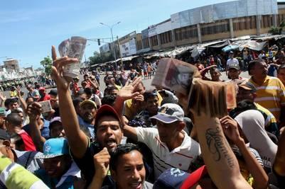 Cientos de personas muestras sus manojos de billetes de 100 bolívares en señal de protesta. (AFP)