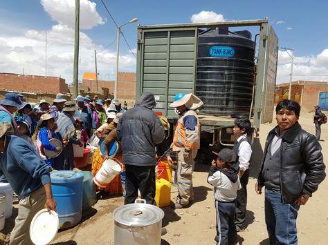 Vecinos del Distrito 7 de El Alto reciben agua de un camión que lleva un tanque de agua.
