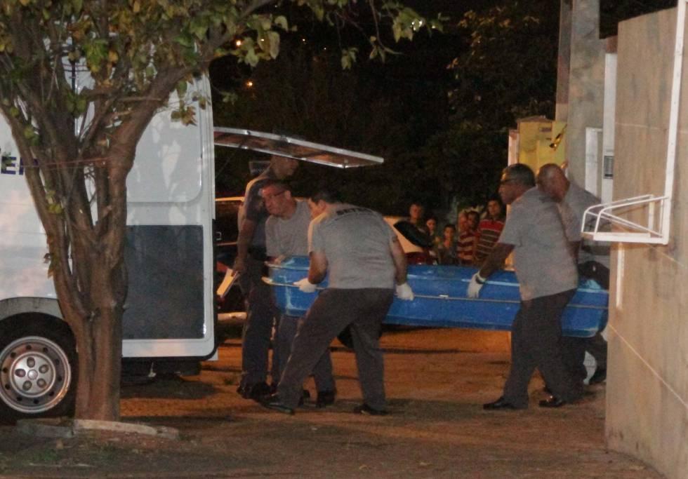 Personal del servicio funerario traslada uno de los cuerpos.
