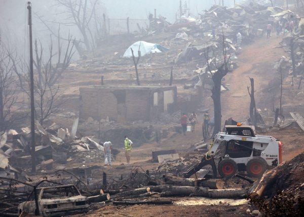 Pobladores comienzan los trabajos de retiro de escombros, el sábado, luego de un incendio forestal en la localidad de Santa Olga, en la región del Maule, al sur de Santiago (Chile).