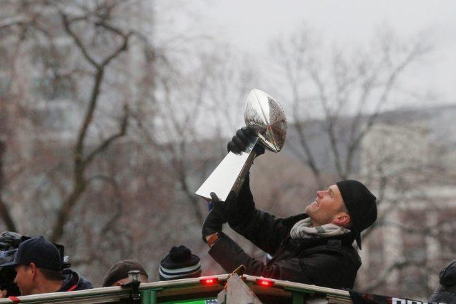 New England Patriots quarterback Tom Brady holds up one of the team